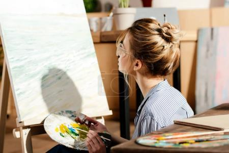 young stylish female artist in eyeglasses using palette and looking at painting