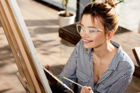 smiling stylish female artist in eyeglasses painting on easel