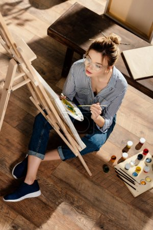 high angle view of stylish female artist in eyeglasses painting on easel