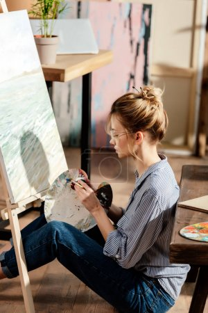 side view of stylish female artist in eyeglasses painting on easel