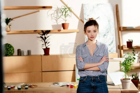 Photo for Portrait of young attractive female artist with crossed arms standing near table with painting supplies - Royalty Free Image