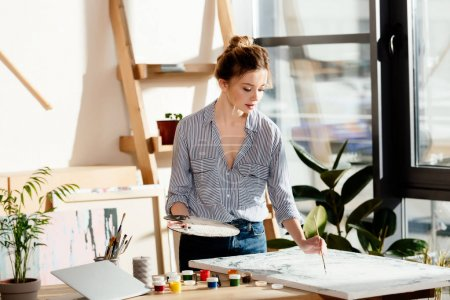 female artist with palette drawing picture by paintbrush