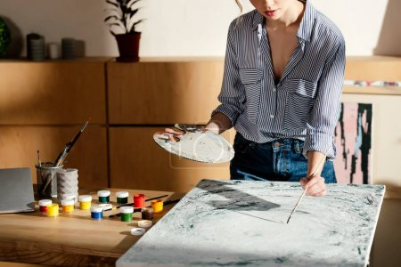 Photo for Cropped image of female artist with palette and paintbrush drawing picture in studio - Royalty Free Image