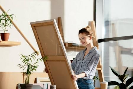 female artist with paintbrush behind ear smiling and looking at own picture