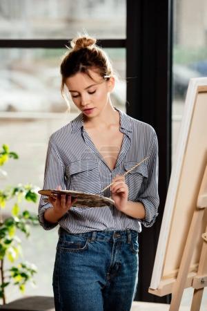 Photo pour Jeune artiste féminine attrayant à l'aide de palette devant chevalet en studio - image libre de droit