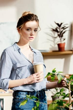 portrait of young woman with paper cup of coffee touching potted plant