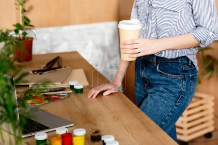 cropped image of female artist with coffee cup standing at table with laptop and painting supplies