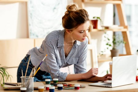 female artist using laptop at table with paintbrushes, palette and paints
