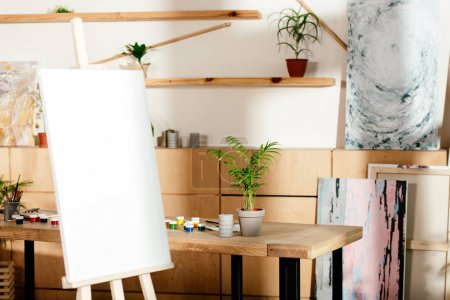 interior of artist studio with easel and table with painting supplies and potted plant