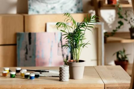 Photo for Closeup shot of potted plant, candle, palette and paints on table in artist studio - Royalty Free Image