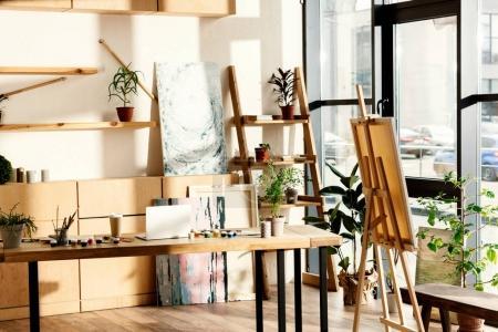 Photo pour Intérieur de l'atelier de l'artiste avec le matériel de peinture et d'ordinateur portable sur la table - image libre de droit