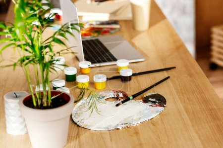 potted plant, paintbrushes, palette, paintbrushes and laptop on table in studio