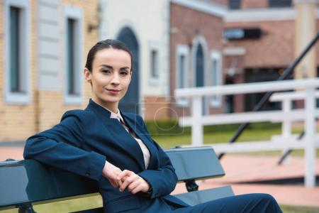 beautiful businesswoman sitting on bench and looking at camera