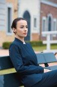 """Постер, картина, фотообои """"красивая деловая женщина, сидя на скамейке в городе и глядя"""""""