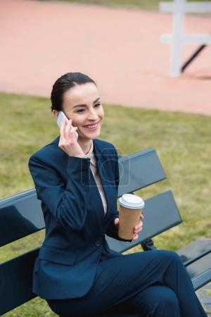 smiling businesswoman talking by smartphone and holding coffee in paper cup on bench