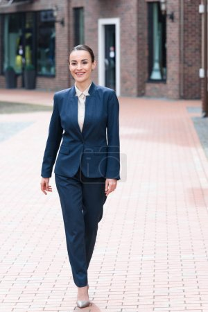 beautiful businesswoman walking on street and looking away