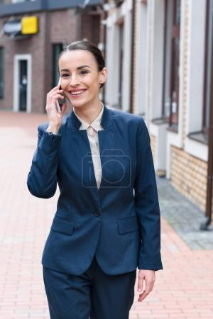Photo for Smiling beautiful businesswoman talking by smartphone in city - Royalty Free Image