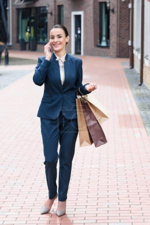 smiling attractive businesswoman holding shopping bags and talking by smartphone