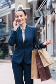 attractive businesswoman gesturing while talking by smartphone and holding shopping bags