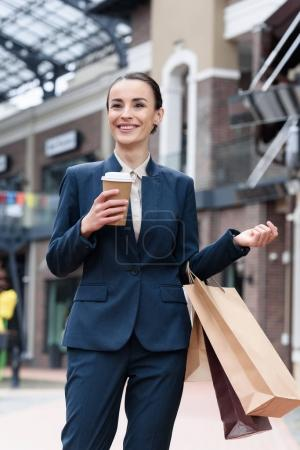 Photo for Attractive businesswoman standing with disposable coffee cup and shopping bags - Royalty Free Image