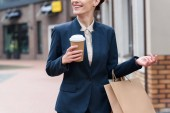 cropped image of businesswoman holding coffee to go and shopping bags