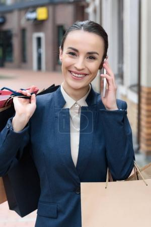 Photo for Attractive businesswoman talking by smartphone and holding shopping bags - Royalty Free Image