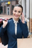 attractive businesswoman talking by smartphone and holding shopping bags