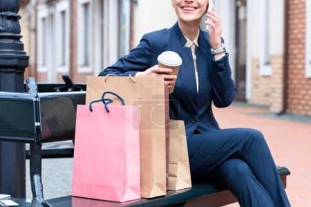 Photo for Cropped image of businesswoman talking by smartphone after shopping - Royalty Free Image