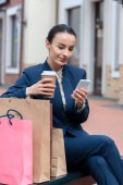 attractive businesswoman using smartphone on bench after shopping