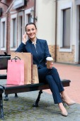 attractive businesswoman sitting on bench with shopping bags and coffee and talking by smartphone