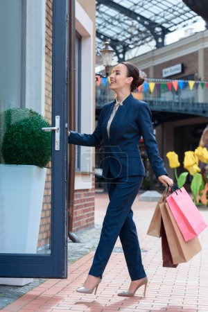 attractive businesswoman with shopping bags opening door to cafe