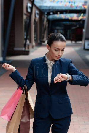 beautiful businesswoman checking time in shopping mall