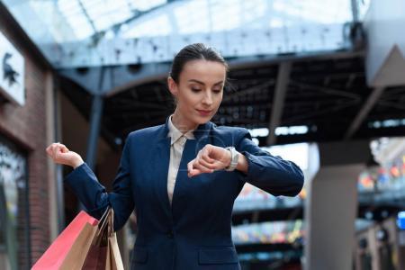 Photo pour Femme d'affaires attrayant vérification temps dans centre commercial - image libre de droit