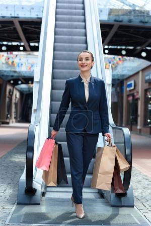 Photo pour Sourire de femme d'affaires attrayant à pied avec les sacs à provisions en centre commercial - image libre de droit