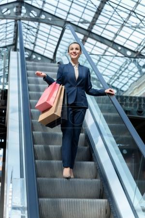 Photo for Low angle view of attractive businesswoman standing on escalator with shopping bags - Royalty Free Image