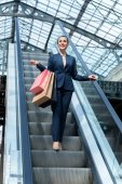 low angle view of attractive businesswoman standing on escalator with shopping bags