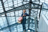 low angle view of attractive businesswoman leaning on railing in shopping mall