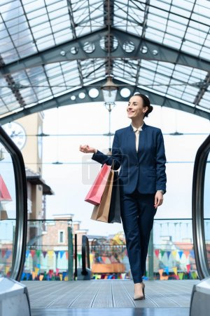Photo for Smiling attractive businesswoman walking with shopping bags in mall - Royalty Free Image