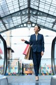 smiling attractive businesswoman walking with shopping bags in mall