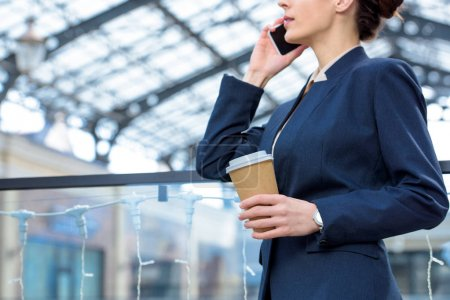 cropped image of businesswoman talking by smartphone and holding coffee in paper cup