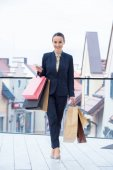 smiling attractive businesswoman standing with shopping bags on mall balcony