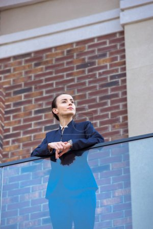 low angle view of beautiful businesswoman standing on balcony and looking away