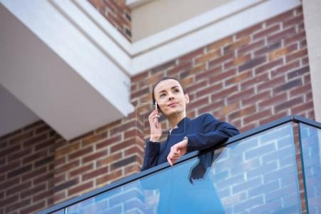 low angle view of beautiful businesswoman standing on balcony and talking by smartphone