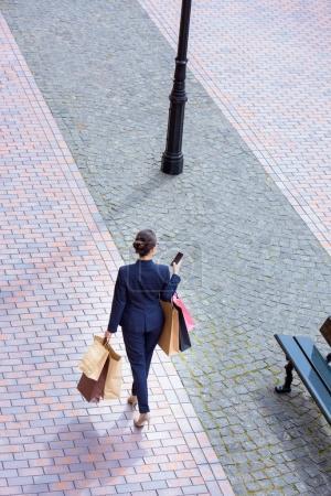 Photo pour Vue d'angle élevé de femme d'affaires marchant avec des sacs à provisions et à l'aide de smartphone - image libre de droit