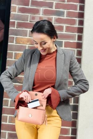 beautiful stylish woman taking credit card from handbag