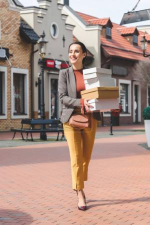 attractive woman with shopping boxes standing on street
