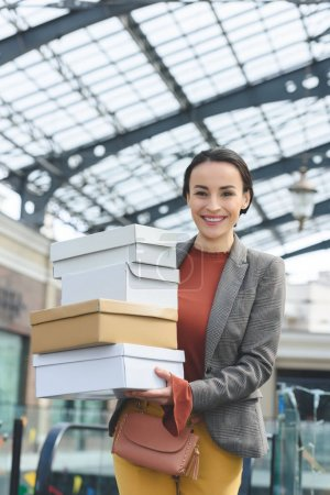smiling attractive woman with shopping boxes looking at camera