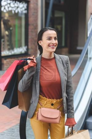 smiling attractive woman standing with shopping bags in mall