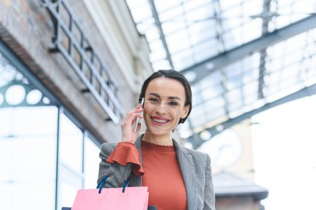 attractive woman talking by smartphone in shopping mall