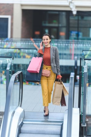attractive woman holding shopping bags and stepping on escalator in mall